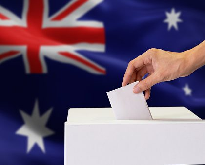 Close-up of human hand casting and inserting a vote and choosing and making a decision what he wants in polling box with Australia flag blended in background